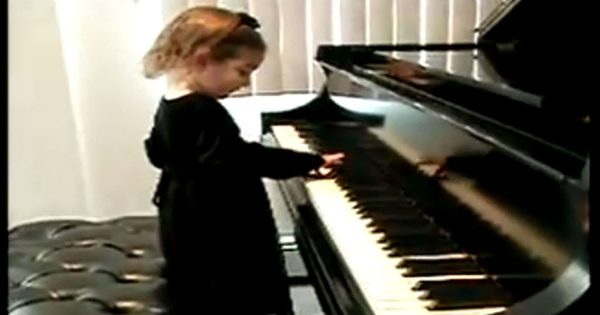 Grandma hears lovely piano music coming from room. she can't believe it when she sees her 2-year-old granddaughter
