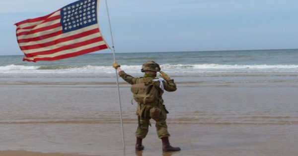 11-year-old boy stands on beach and holds salute for 1 hour, but who joins him moved everyone to tears