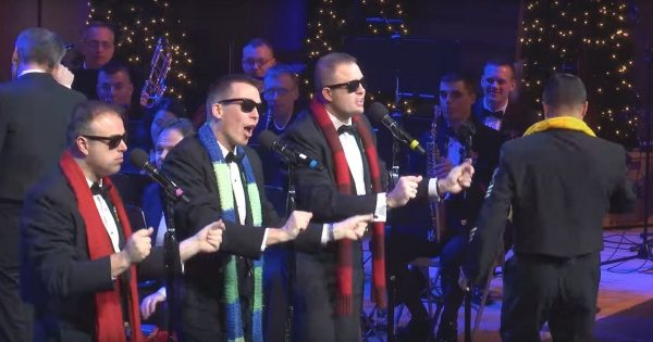 Soldiers in Sunglasses Perform Christmas Hit – Then Man In Yellow Scarf Grabs Mic and Leaves Audience in Awe
