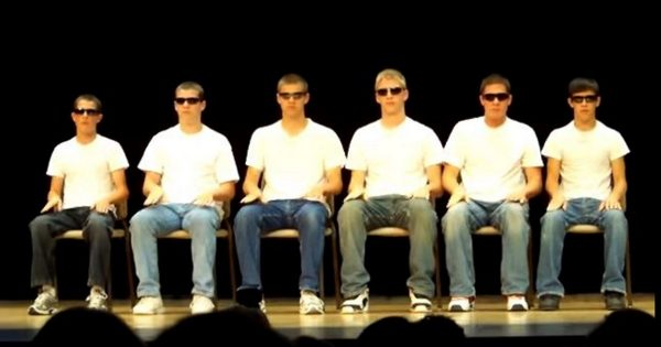 6 boys with sunglasses line up silently on stage. Seconds later, boy on left snaps and everything changes
