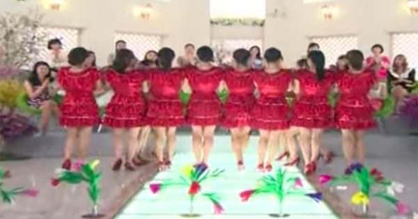 Women line up in matching red dresses. When they turn around the audience gasps in disbelief