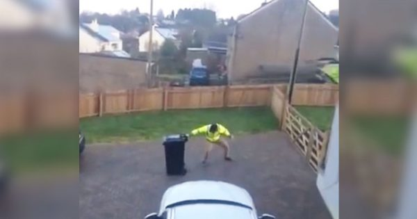 Man struggles to move trash can through icy driveway. Wife captures moment that has everyone cracking up