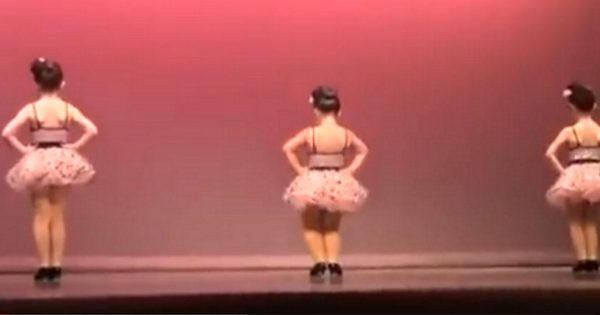 3 little girls line up on stage facing wall.  But wait until the girl in the middle turns around