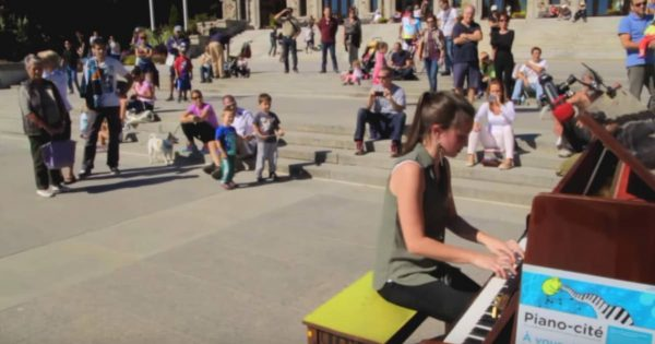 Young woman sits on public piano. Her rendition of 'Bohemian Rhapsody' has whole crowd looking on in complete awe