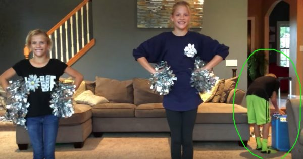 Sisters prepare to show off cheer routine, but they have no idea young brother's seconds away from stealing show