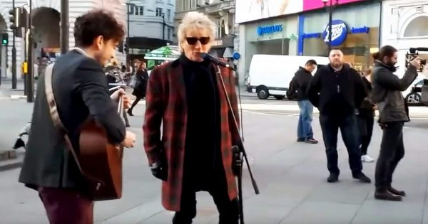 Mysterious man asks street performer to join in, then crowd freeze in their tracks upon hearing familiar voice