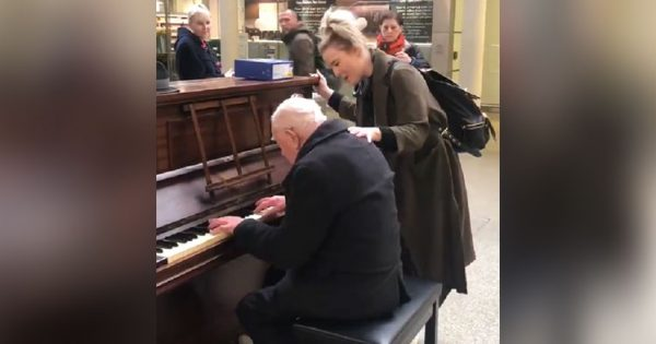 91-yr-old man sits to play piano alone at train station, only for unlikely partner to stop & sing