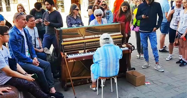Old lady takes seat at street and makes everybody's eyes pop moment she starts to play